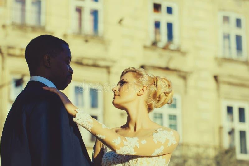 Älska par av den gulliga brud- och afrikansk amerikanbrudgummen royaltyfri fotografi