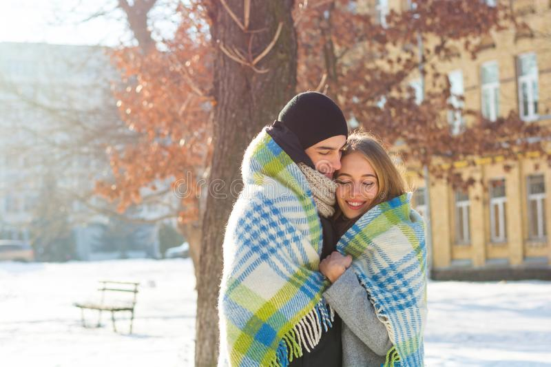 Älska par i en filt i vinter Grabben kramar en flicka på gatan i vinter arkivbilder