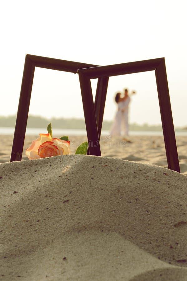 Älska par i fotoram på sand arkivbilder