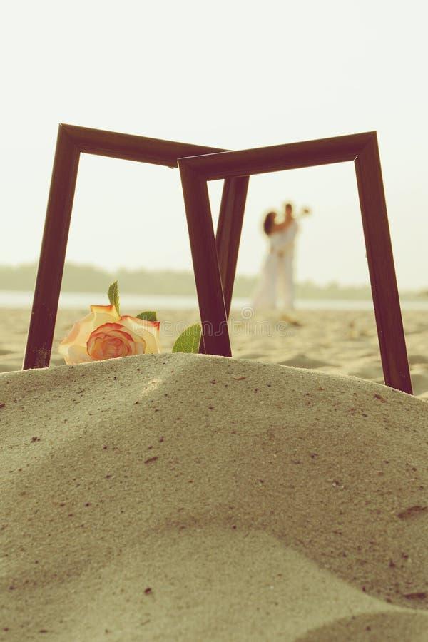 Älska par i fotoram på sand royaltyfri fotografi
