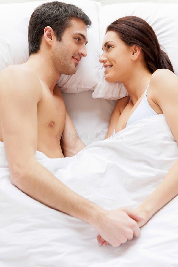 Älska par i säng. fotografering för bildbyråer