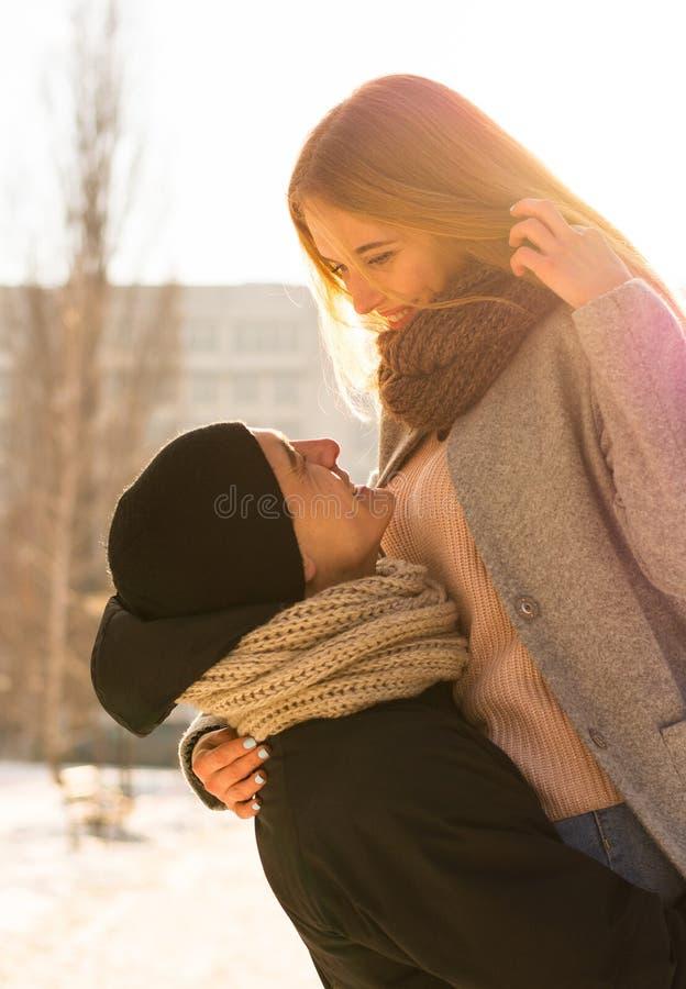 Älska par i vinter Grabben lyfter en flicka i hans armar på gatan i vinter arkivfoto