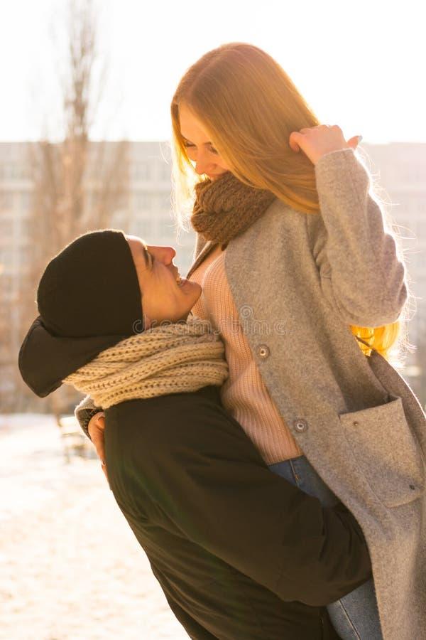 Älska par i vinter Grabben lyfter en flicka i hans armar på gatan i vinter arkivbilder