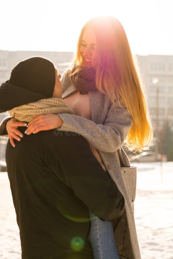 Älska par i vinter Grabben lyfter en flicka i hans armar på gatan i vinter royaltyfri fotografi
