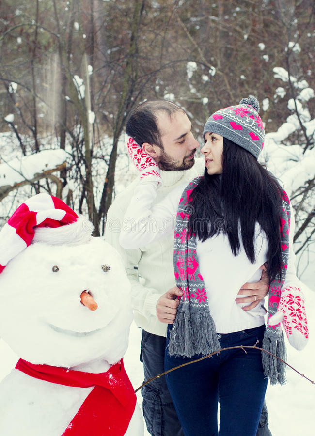Älska par i vinterskogen royaltyfri foto