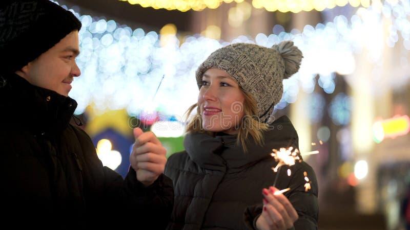 Älska par med att le för tomtebloss som ser in i ögon i vinterstad på natten, det glade Christmass och för nytt år begreppet arkivfoto