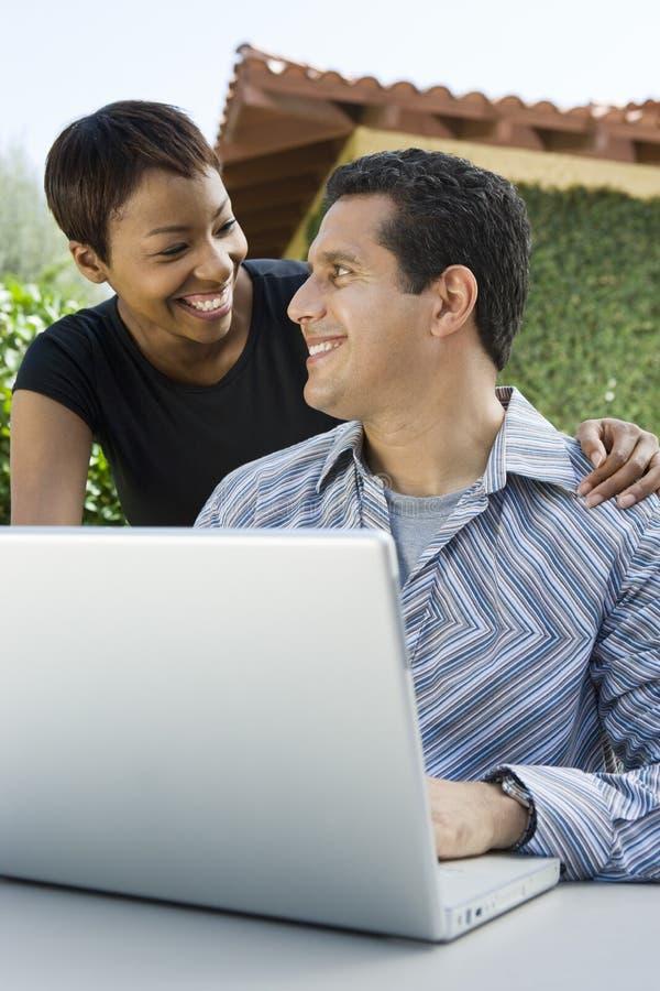 Älska par med mannen som använder bärbara datorn arkivbilder