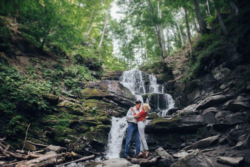 Älska par nära en vattenfall i skog royaltyfria foton