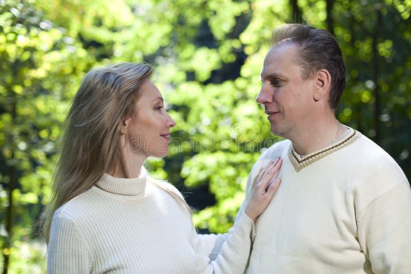 Älska par på en bakgrund av grön lövverk royaltyfria foton