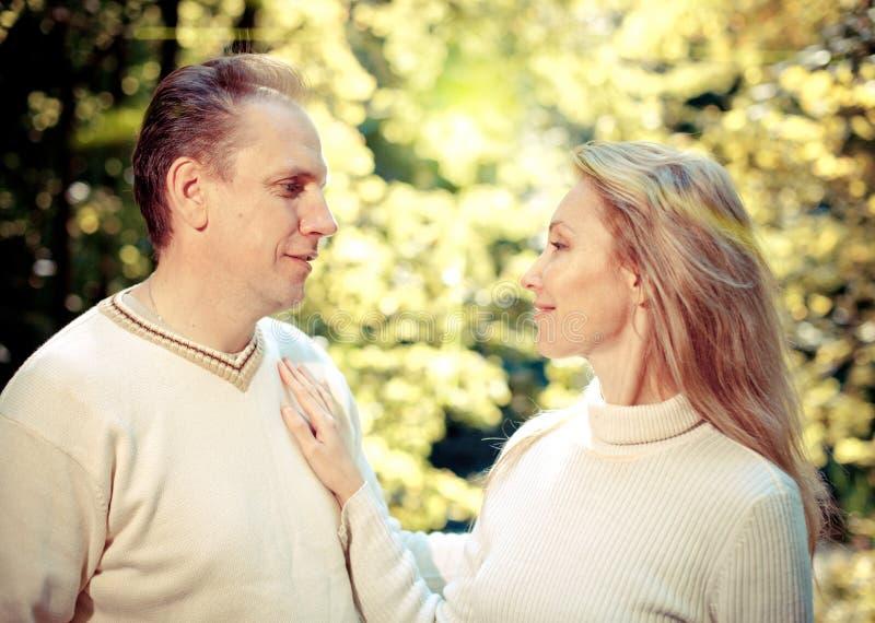 Älska par på en bakgrundslövverk med en retro effekt royaltyfria bilder