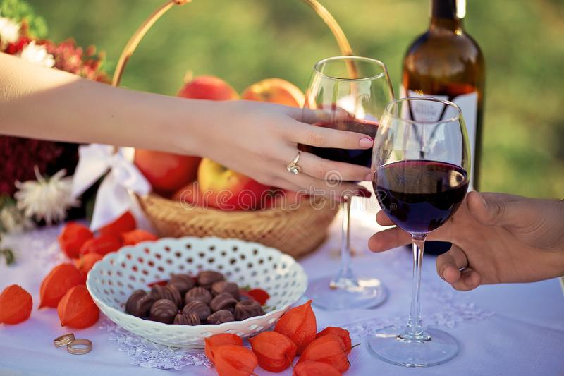 Älska par som dricker rött vin från genomskinliga exponeringsglas, bröllopdag, utomhus- picknick med den söta godisen och frukt arkivbild