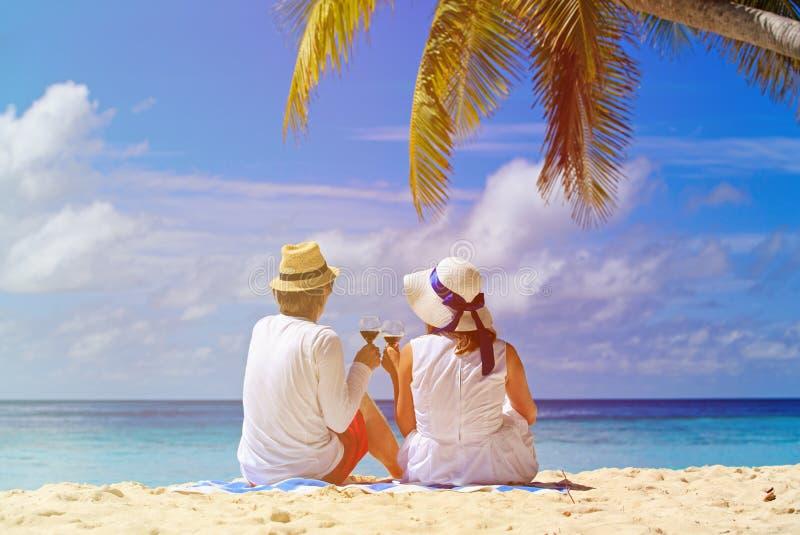 Älska par som dricker vin på den tropiska stranden arkivbilder