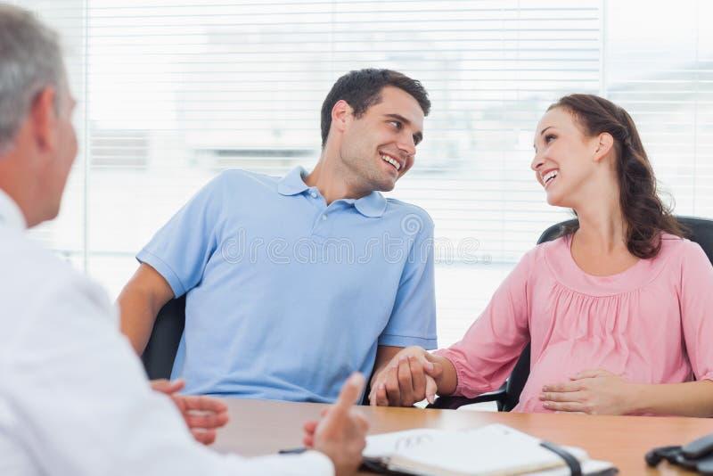 Älska par som förväntar, behandla som ett barn den konsulterande doktorn arkivfoton