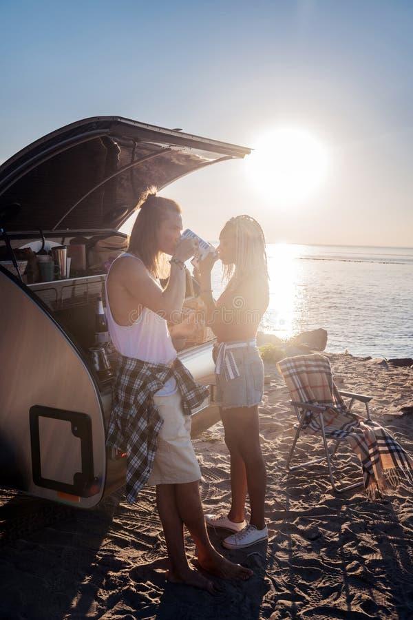 Älska par som har frukosten nära hållande ögonen på soluppgång för husvagn som används som permanent hem royaltyfria bilder