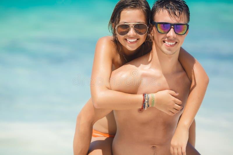 Älska par som har gyckel på stranden av havet. arkivfoton
