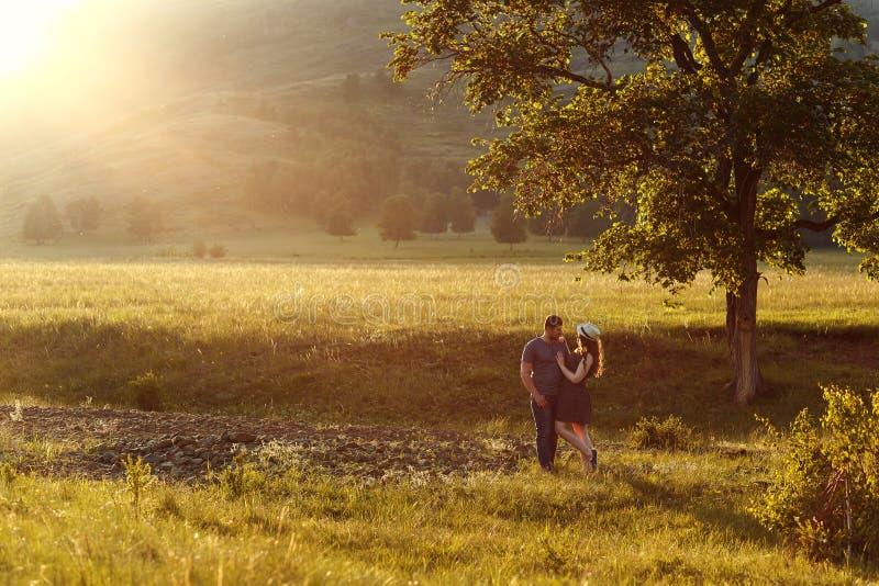 Älska par som kramar, bröllopsresa i bergen, landskapet, de varma färgerna av inställningssolen, panelljus, berg, summe royaltyfri foto