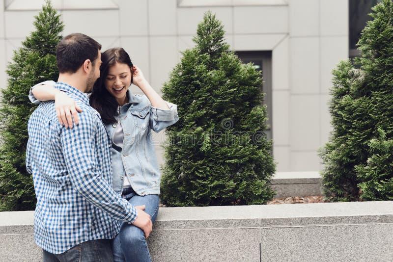 Älska par som kramar sammanträde på balustraden royaltyfri bild