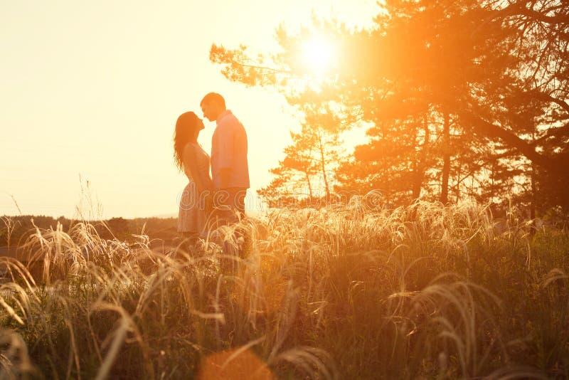 Älska par som kysser på solnedgången royaltyfria foton