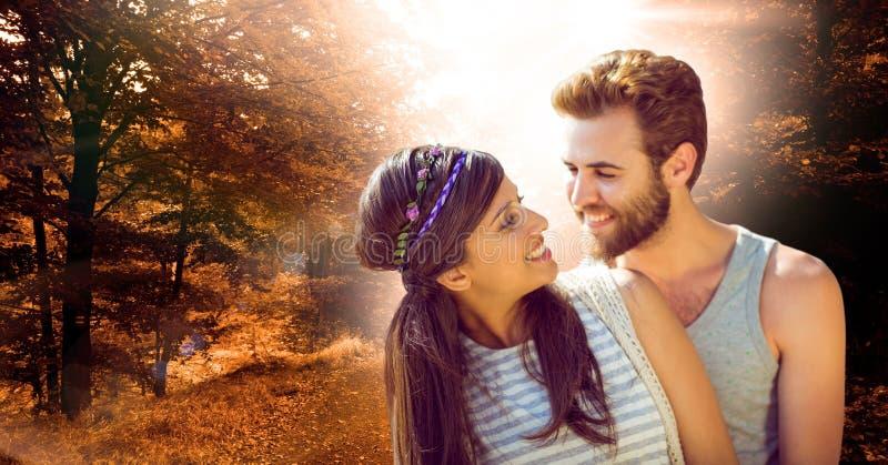 Älska par som ler i skog under höst royaltyfria foton