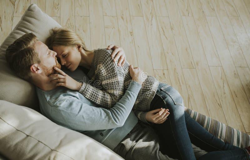 Älska par som ner ligger på soffan i rummet royaltyfria bilder