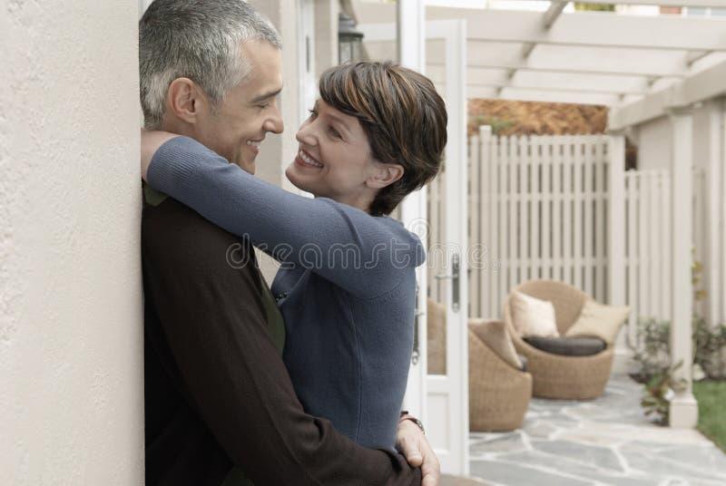 Älska par som omfamnar på farstubron arkivfoton