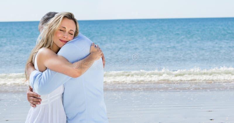 Älska par som omfamnar på stranden royaltyfri bild