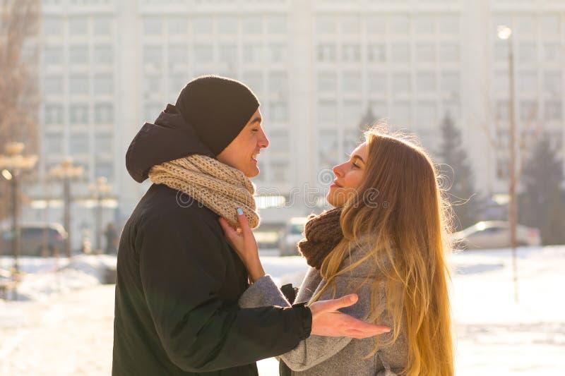 Älska par som ser de och att skratta plädet i vinter Grabben kramar en flicka på gatan i vinter royaltyfri fotografi
