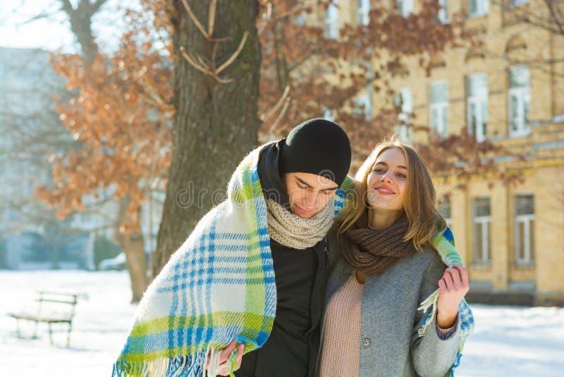 Älska par som ser de och att skratta plädet i vinter Grabben kramar en flicka på gatan i vinter royaltyfria foton
