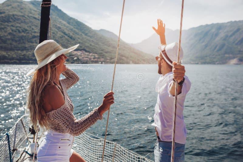 Älska par som spenderar lycklig tid på en yacht på havet royaltyfria foton