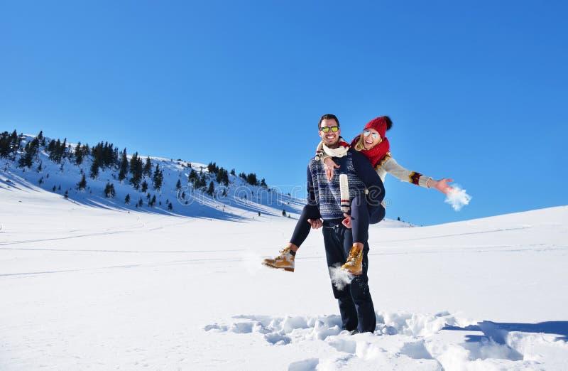 Älska par som tillsammans spelar i utomhus- snö royaltyfri foto