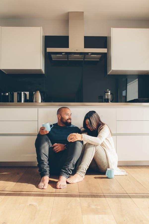 Älska par som tycker om ett kaffe på kökgolv arkivfoto