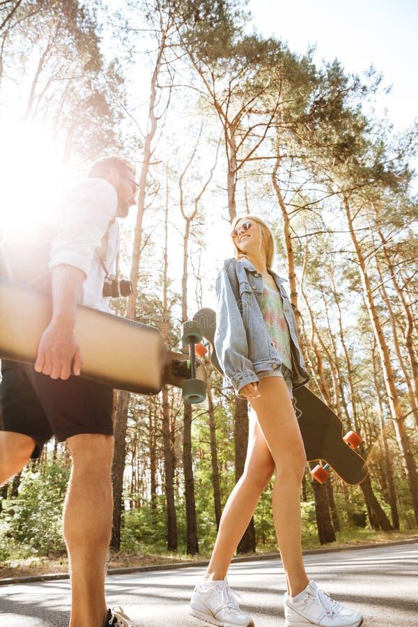 Älska par som utomhus går med skateboarder åt sidan se royaltyfria bilder