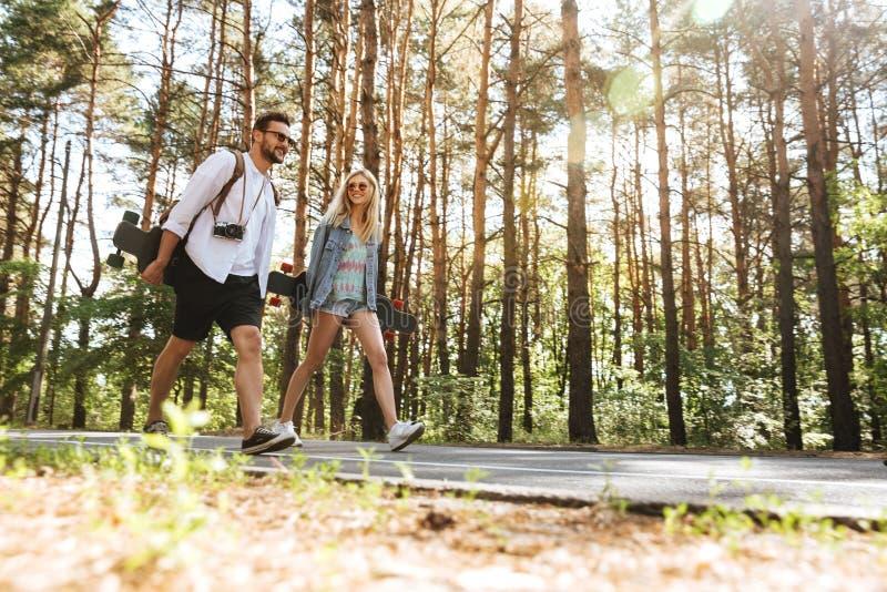 Älska par som utomhus går med skateboarder fotografering för bildbyråer