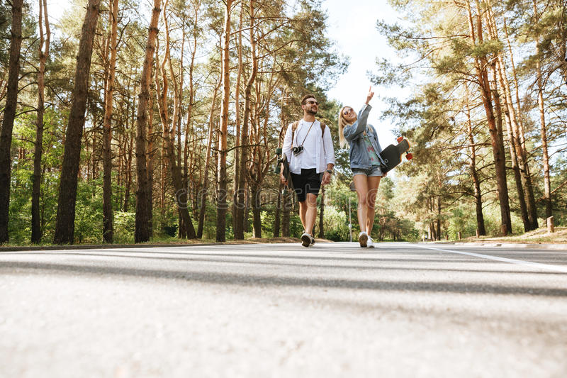 Älska par som utomhus går med skateboarder royaltyfri foto