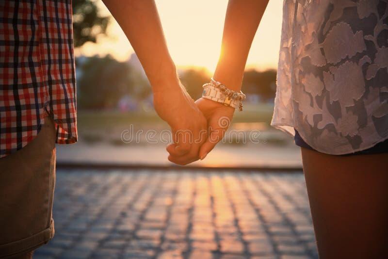 Älska parinnehavhänder, medan gå på solnedgången royaltyfria bilder