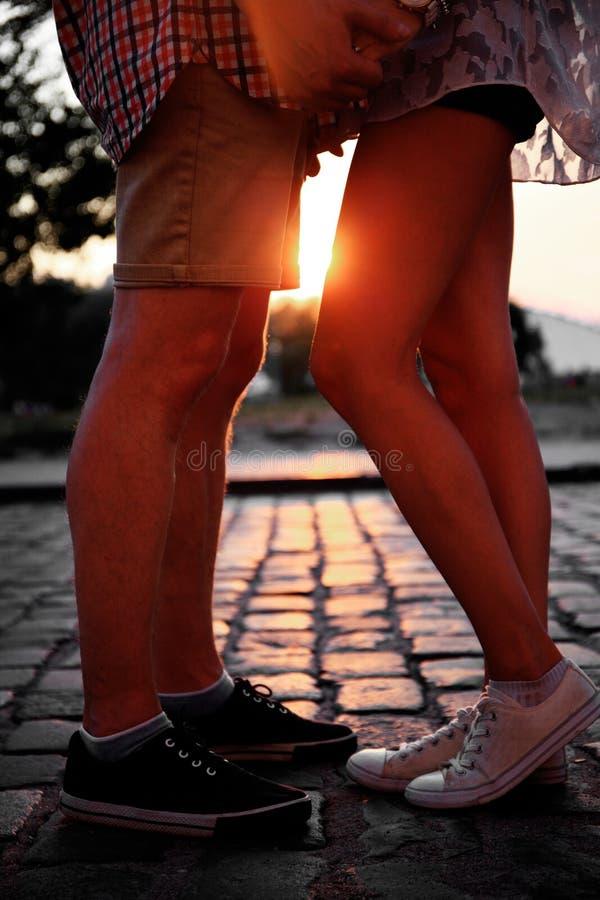 Älska parinnehavhänder, medan gå på solnedgången royaltyfri bild