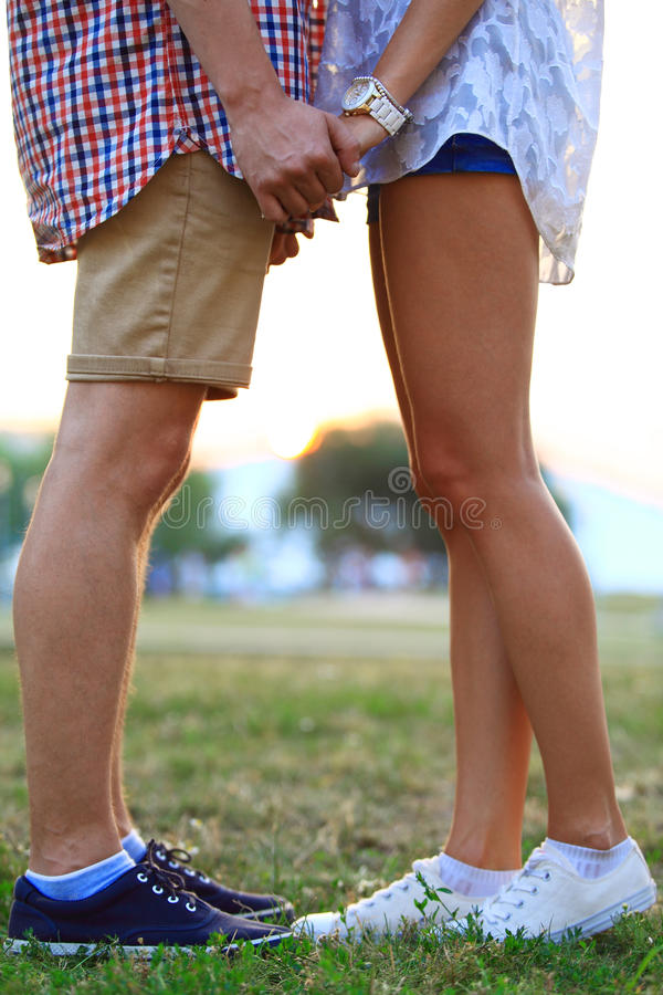 Älska parinnehavhänder, medan gå på solnedgången royaltyfria foton