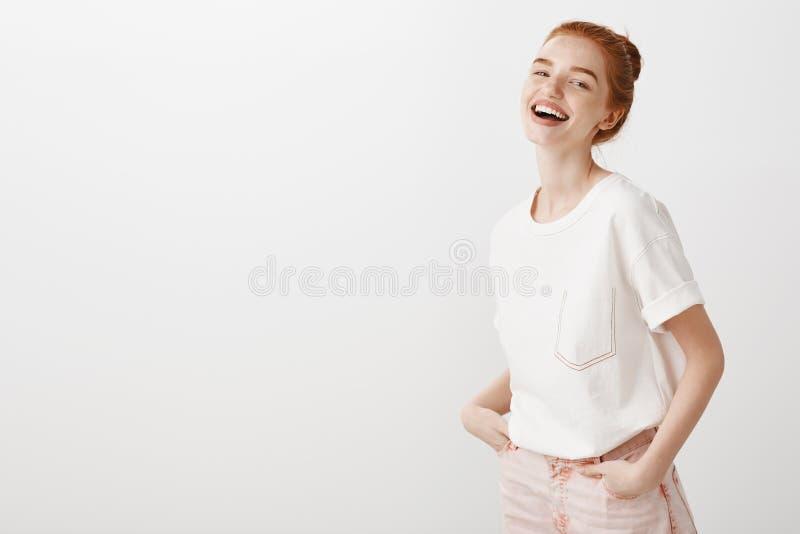 Älska personen gör alltid mig att skratta Stilfull ljust rödbrun flicka i moderiktig jeans och vita t-skjortan som rymmer händer  arkivfoto