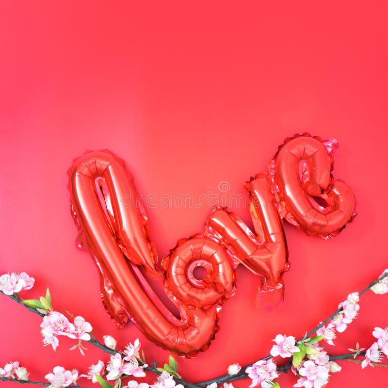 älska röd folieballong med rosa sakura på röd arkivbild