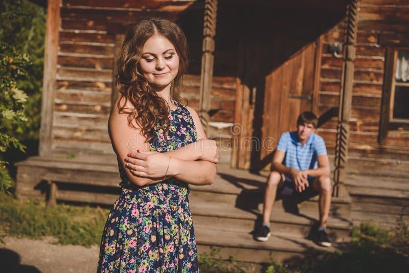 Älska romantiska par i byn, nära ett trähus En man sitter på farstubron, en ung kvinna i förgrunden arkivfoton