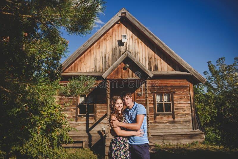 Älska romantiska par i byn, nära ett trähus Mannen omfamnar en ung kvinna Begrepp: förälskelse romans, sommar royaltyfri bild
