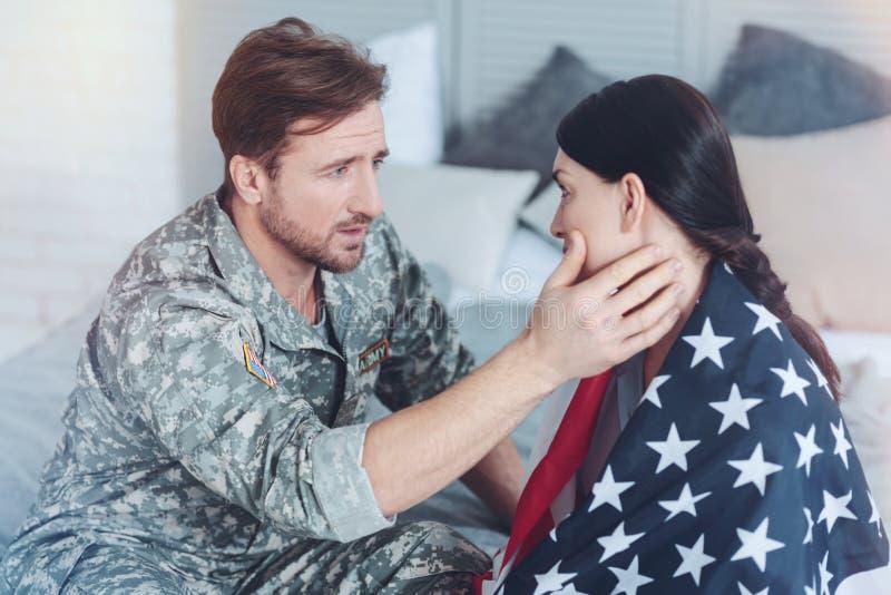 Älska soldaten som lugnar hans bekymrade fru, innan att lämna royaltyfri foto