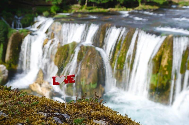 Älska text på en pinne ovanför vattenfallet close upp arkivfoto