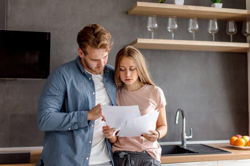 Älska unga enorma par som usinganalyzing deras finanser med dokument arkivbild