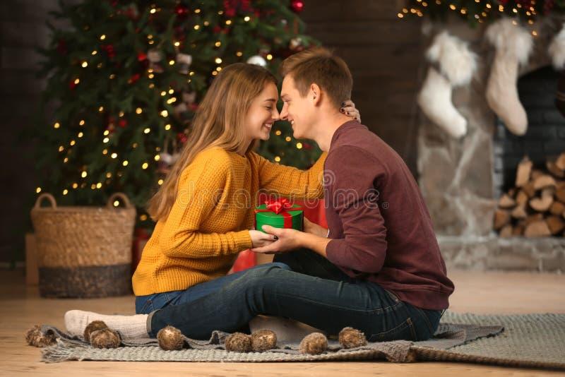 Älska unga par med gåvan i rum med juldekoren arkivfoto