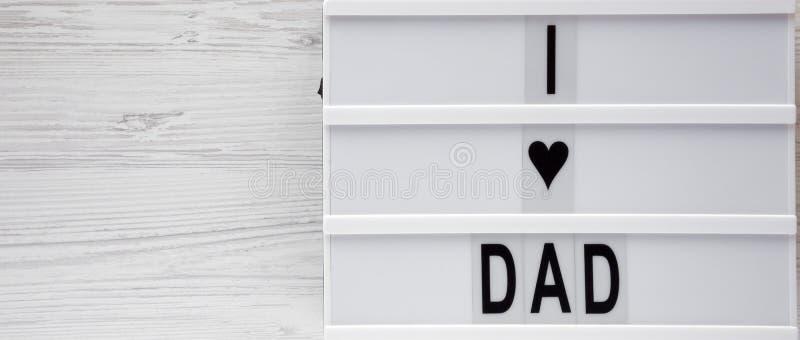 'Älskar jag farsa'ord på en ljus ask över vit träbakgrund, bästa sikt ?ver huvudet fr?n ?ver, framl?nges lekmanna- kopiera avst?n arkivbilder