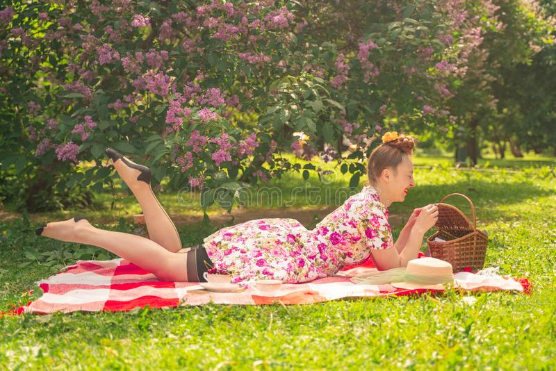 Älsklingen som charmar utvikningsbrudflickan i en sommarklänning på en rutig filt i, parkerar nära buskarna av lilan tycker om li arkivfoto
