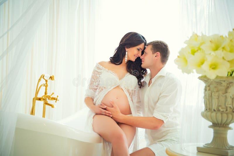 Älsklingföräldrarna Gravida par för mjuk kyss royaltyfri foto