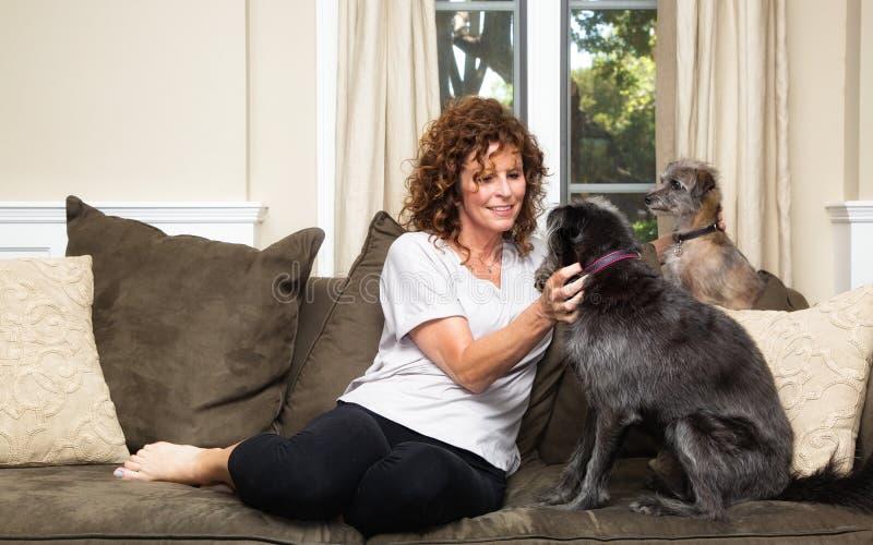 Älsklings- barnvakt på soffan som daltar hundkapplöpning royaltyfri fotografi