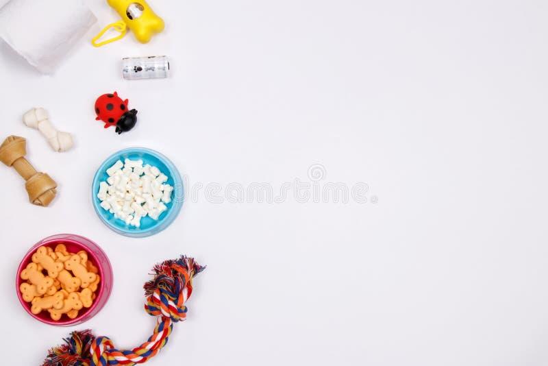Älsklings- tillbehör, mat och leksak på vit bakgrund Lekmanna- lägenhet överkant arkivbilder